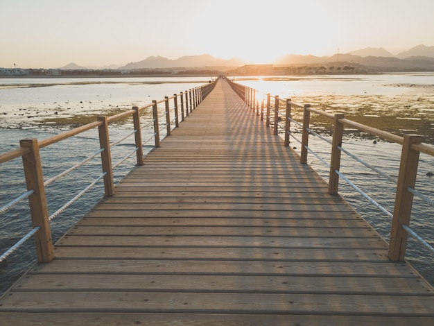 Schöne aussicht auf den sonnenuntergang über dem meer, den bergen und dem langen holzsteg