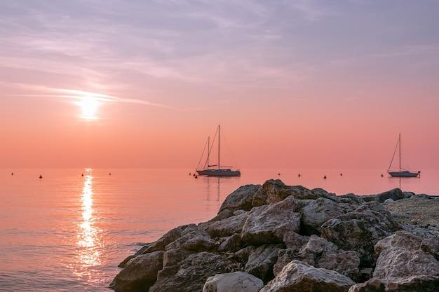 Schöne aussicht auf den sonnenuntergang während des nebels am gardasee mit segelbooten und strukturierten steinen im vordergrund