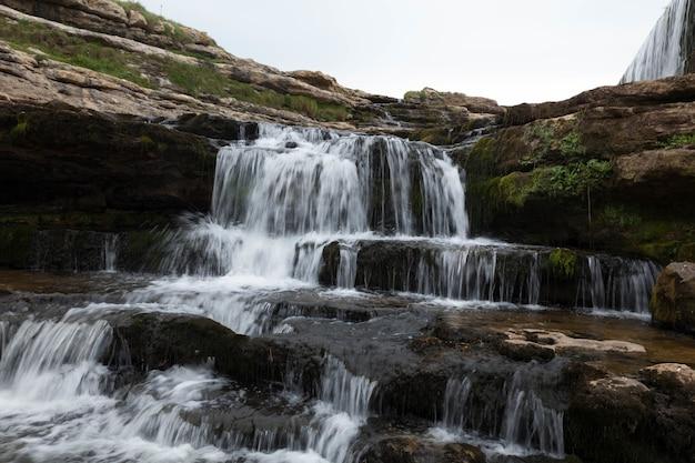 Schöne aussicht auf den wasserfall, der die mit moos bedeckten klippen hinunterströmt