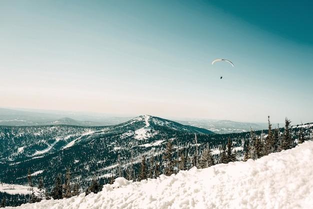 Schöne aussicht auf die berge am sonnigen tag mit skifahrern und snowboardern unter blauem himmel mit sonnenlicht im winter.