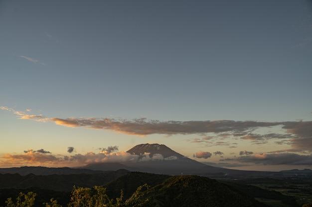Schöne aussicht auf die hügelwiese und den schlafenden vulkan, umgeben von wolken stockfoto