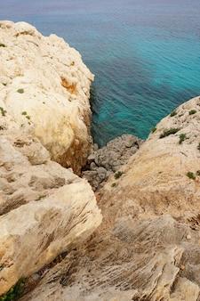 Schöne aussicht auf die klippe in der nähe des ufers eines ruhigen ozeans