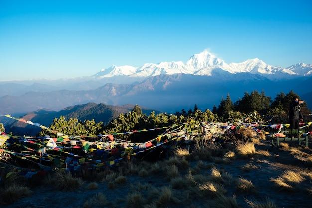 Schöne aussicht auf die landschaft des himalaya-gebirges. schneebedeckte berggipfel und mehrfarbige tibetische gebetsfahnen. trekkingkonzept in den bergen