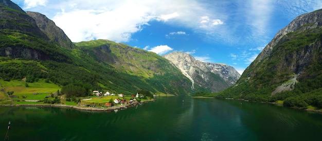 Schöne aussicht auf die natur mit grünem wald in den bergen, mit dorfhäusern am norwegischen seekanalwasser auf blauem himmelshintergrund