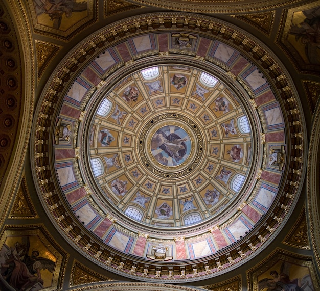 Schöne aussicht auf die runde kuppel der katholischen kathedrale im inneren mit farbenfrohen wandgemälden und fresken in budapest ungarn.
