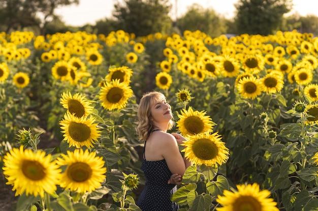 Schöne aussicht auf ein mädchen, das an einem sommertag neben sonnenblumen auf dem feld posiert