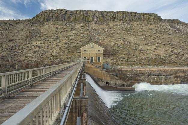 Schöne aussicht auf eine holzbrücke über den fluss in richtung eines hauses in der nähe des berges