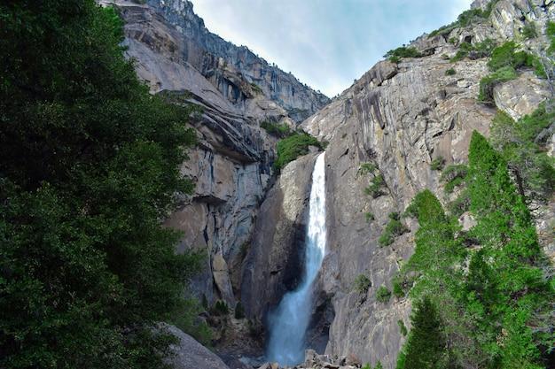 Schöne aussicht auf einen wasserfall, der von einem felsen fließt und in die herrliche grüne landschaft gießt