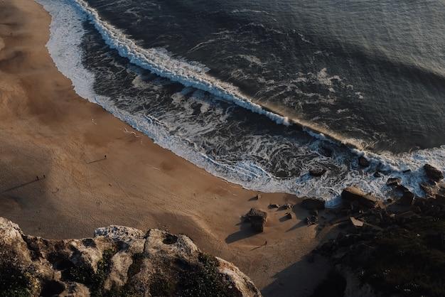 Schöne aussicht auf große wellen, die an einem strand bei sonnenuntergang abstürzen