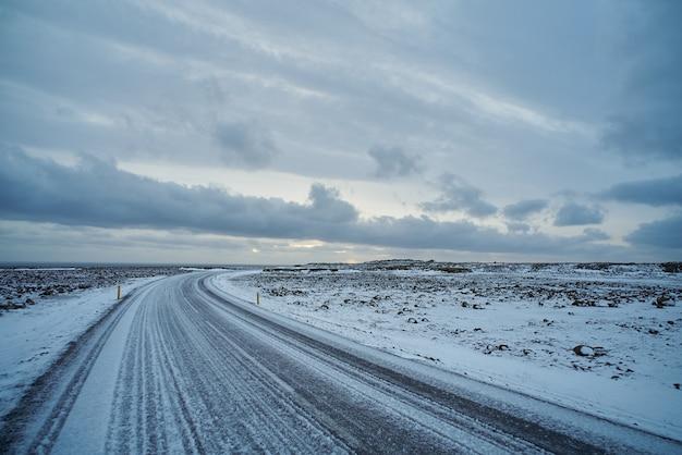 Schöne aussicht auf leere gefrorene straße mit eis in island. ozean weit weg, wolken am himmel, böses winterwetter