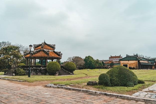 Schöne aussicht auf traditionelle vietnamesische pavillons auf blauem himmelshintergrund im garten der kaiserstadt am sonnigen sommertag in hue, vietnam. hue ist ein beliebtes touristenziel in asien.