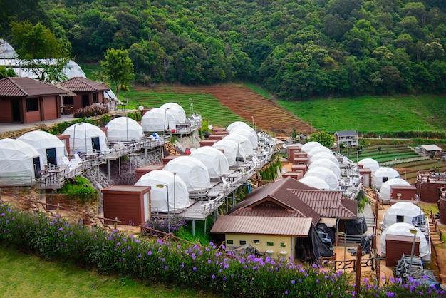 Schöne aussicht auf weiße campingzelte mit mon jam berglandschaft und resorts bei sonnenaufgang am morgen.