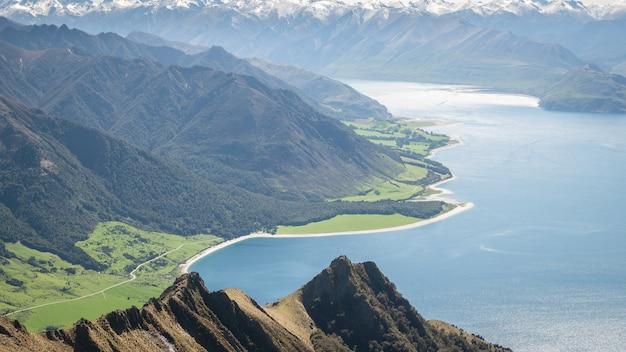 Schöne aussicht mit trockenen büscheln sattgrüne wiesen blauer see und schneebedeckte berge neuseeland