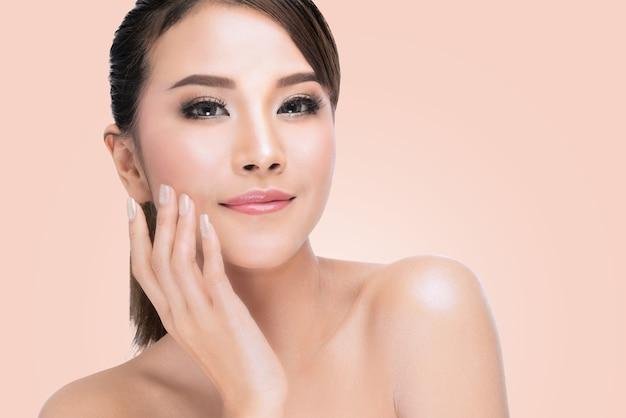 Schöne badekurort-asiatin, die ihr gesicht berührt. perfekte frische haut. reines schönheits-modell.