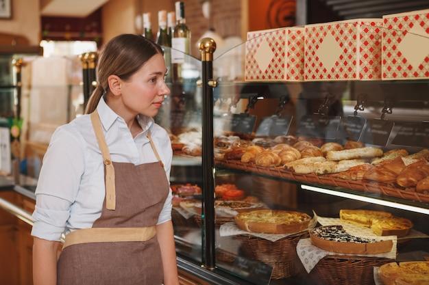 Schöne bäckerin, die an ihrem bäckereigeschäft geht und gebäck auf dem display betrachtet, kopiert raum