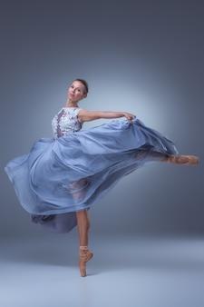 Schöne ballerina, die im langen blauen kleid auf blauem hintergrund tanzt