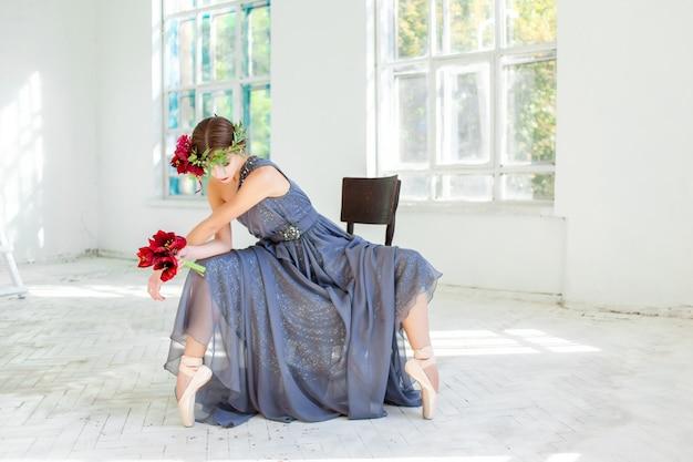 Schöne ballerina, die im langen grauen kleid sitzt