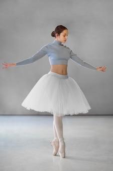 Schöne ballerina, die im tutu-rock tanzt
