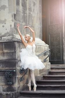 Schöne ballerina, die nahe einem alten gebäude tanzt