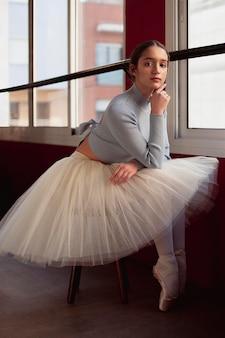 Schöne ballerina im tutu-rock, der neben fenster aufwirft