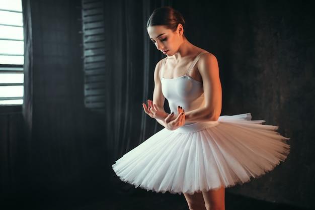 Schöne ballerina im weißen kleid, das im studio tanzt. klassische balletttänzerausbildung im unterricht