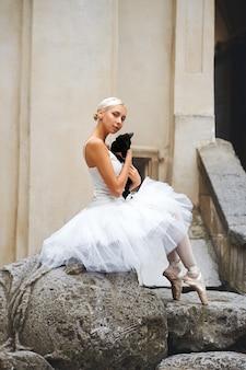 Schöne ballerina streicheln schwarze katze