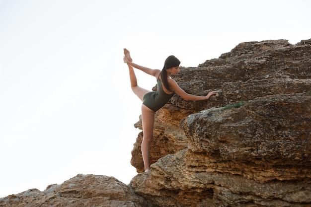 Schöne ballerina tanzen, posiert auf felsen am strand, meerblick.