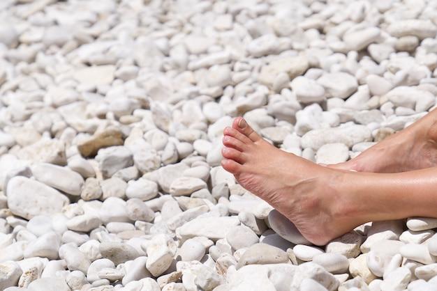 Schöne beine auf einem felsigen strandfrauenfüße vor dem felsigen strand des meeres