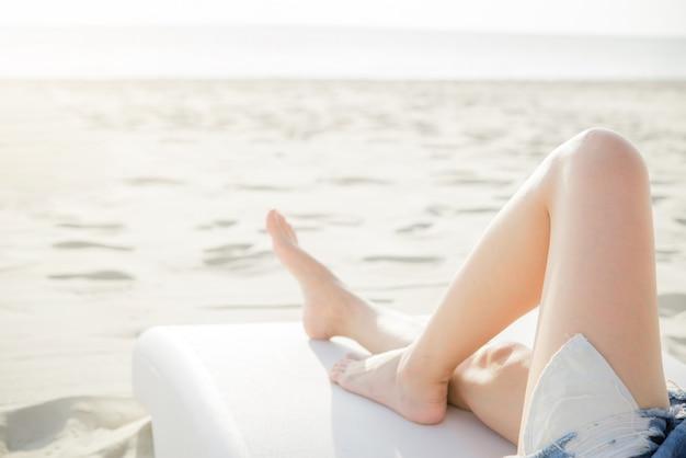 Schöne beine der jungen frau, die auf dem strand stillstehen und sich entspannen