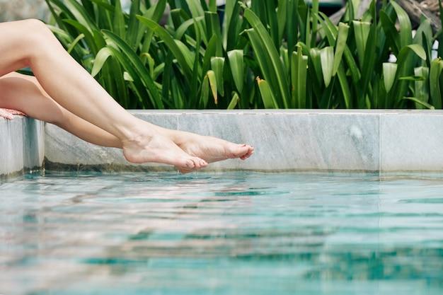 Schöne beine der jungen frau, die wasser im schwimmbad spritzt