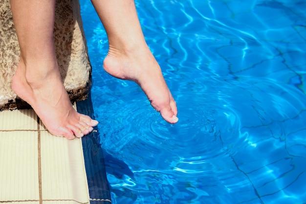 Schöne beine eines mädchens in der nähe eines swimmingpools auf dem meereshintergrund