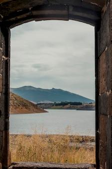 Schöne berglandschaft mit antikem steinfenster eingerahmt