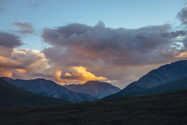 Schöne berglandschaft mit goldenem morgenlicht bei bewölktem himmel. malerische berglandschaft mit leuchtender farbe im sonnenuntergangshimmel. silhouetten von bergen bei sonnenaufgang. gold leuchtendes sonnenlicht im himmel