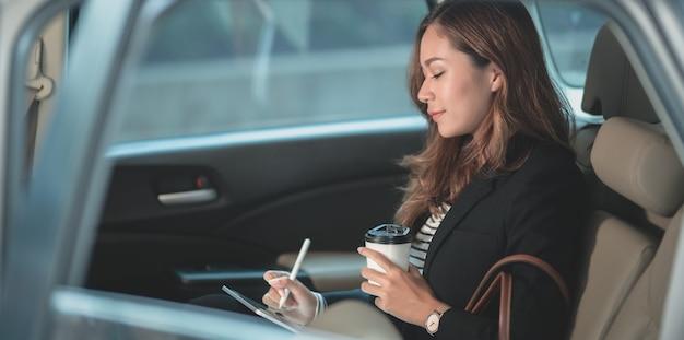 Schöne berufsgeschäftsfrau, die an dem auto bei der überschrift zum büro arbeitet