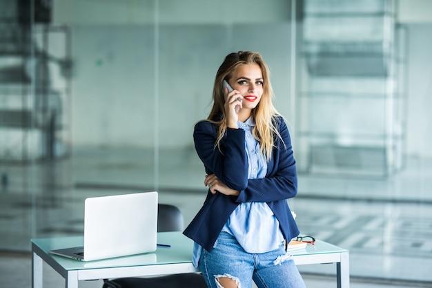 Schöne beschäftigte geschäftsfrau, die im büro steht, im planer schreibt und auf handy spricht.
