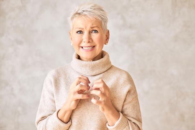Schöne besorgte pensionierte frau, die kuscheligen pullover und kurze frisur trägt