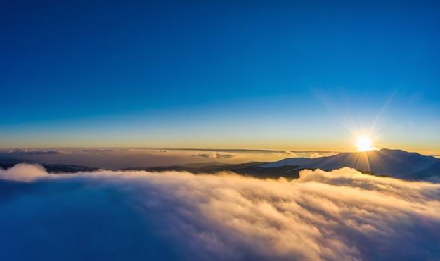 Schöne bezaubernde aussicht auf berge und felsen mit fichtenwald an einem frostigen winterabend mit nebel und sonnenuntergangssonne. naturkonzept des harten winters