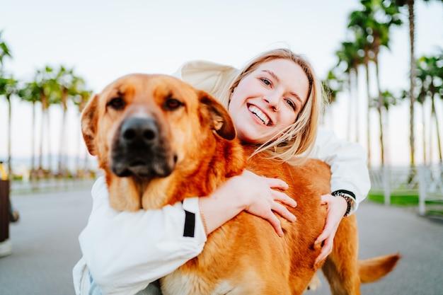 Schöne blauäugige blondine in einer weißen windjacke umarmt einen großen schönen roten hund vor dem hintergrund von palmen