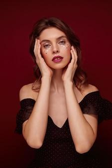Schöne blauäugige junge brünette dame, die festliches make-up und elegante kleidung trägt, sanft ihr gesicht mit erhobenen händen hält und schaut