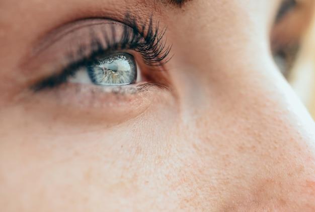Schöne blaue augen der jungen frau des make-up