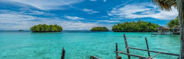 Schöne blaue lagune mit einigen bambushütten, kordiris gastfamilie, palmtree vor, gam island, west papuan, raja ampat, indonesien.