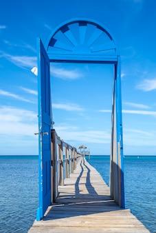 Schöne blaue tür auf einem hölzernen gehweg auf der karibikinsel roatan in honduras, vertikales foto