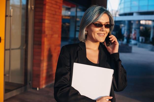 Schöne blauhaarige geschäftsfrau, die laptop außerhalb tolles design für alle zwecke hält...
