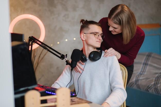 Schöne blod haarfrau umarmen seinen ehemann während der arbeit am computer glückliches paar, das zu hause arbeitet