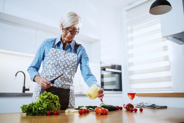 Schöne blonde ältere frau in der schürze, die in der küche steht und gesunde mahlzeit vorbereitet