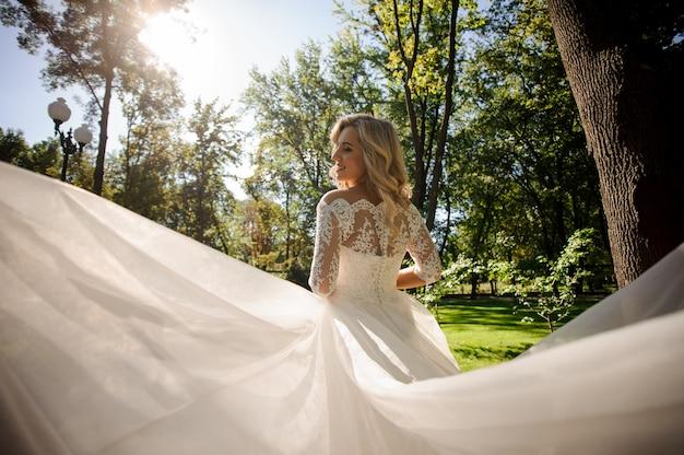 Schöne blonde braut, die im reizenden weißen hochzeitskleid wirbelt