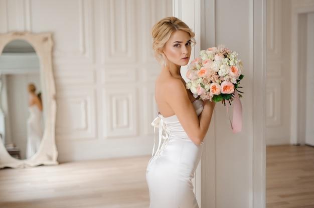 Schöne blonde braut im eleganten weißen kleid, das einen hochzeitsblumenstrauß hält