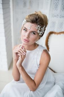 Schöne blonde braut mit hohem haar-tun und kostbarem silbernem kranz auf ihrem haar