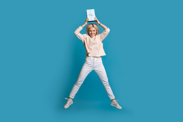 Schöne blonde dame, die auf eine blaue studiowand springt, die eine schachtel mit geschenk hochhält