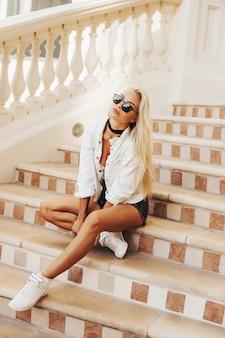 Schöne blonde dame, die durch die stadt dubai emirate bereist. stadtrundfahrt fotografie im golfland. städtischer stadtlebensstil der arabischen nation.